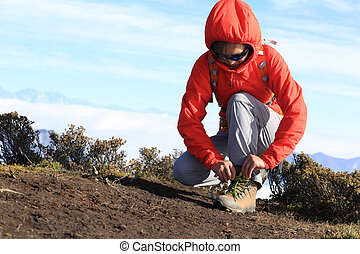 young woman hiker tying shoelace of hiking boots on mountain peak