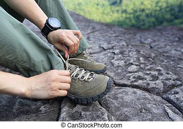 Young woman hiker tying shoelace on mountain peak