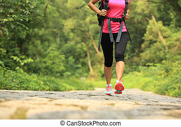 young woman hiker walking on trail - young fitness woman...