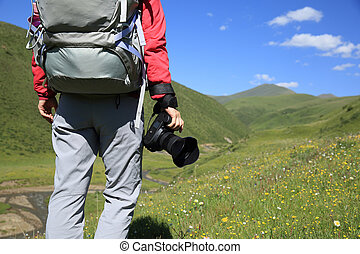 young woman hiker walking with camera in mountains