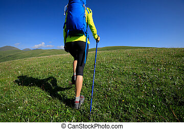 young woman hiking in grassland mountain top