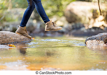 young woman hiking in mountain crossing stream