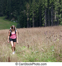 young woman hiking outdoors (going uphill) - young woman...