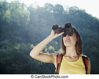 young woman hiking with binoculars