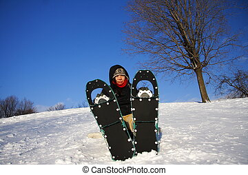 Young woman hiking with Snowshoes / Rackets