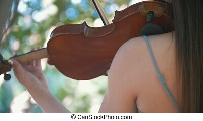 Young woman hipster playing a violin standing among the tree...