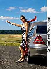 woman hitch-hiking - young woman hitch-hiking beside a...