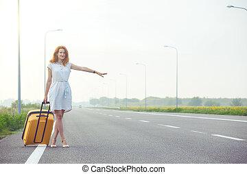 young woman hitch-hiking