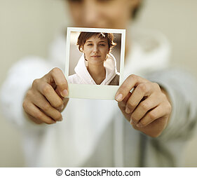 photo - young woman hold self-portrait, selective focus on...