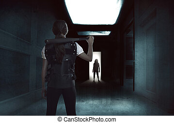 Young woman holding a baseball bat standing in a dark hallway with zombie