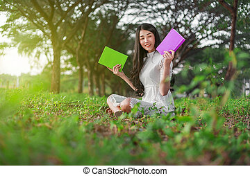 young woman holding a book in park