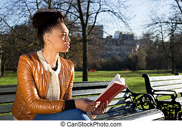 young woman holding a book looking thoughtful