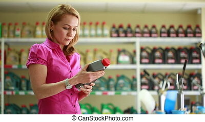 Young woman holding a bottle of motor oil. Girl chooses to car oil.