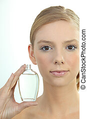 Young woman holding a bottle of perfume