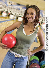 Young woman holding a bowling ball in a bowling alley