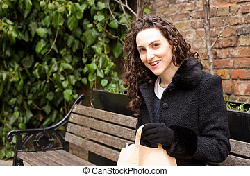 young woman holding a brown sandwich bag sitting on a bench