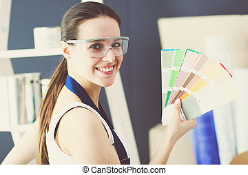 Young woman holding a color swatch with a painter painting .