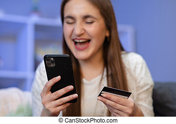 Young woman holding a credit card and doing online payment with smartphone at home. Online shopping concept.