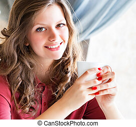 Young woman holding a cup of coffee in hand, sitting in a cafe and smiling