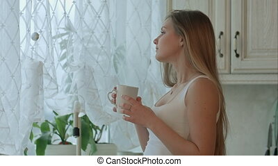 Young woman holding a cup of coffee in her kitchen