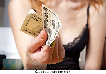 Young woman holding a dollar in her hand