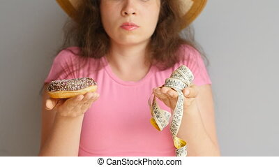 Young woman holding a donut and a measuring tape