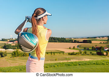 Young woman holding a driver club during golf swing at the begin