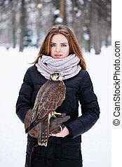 woman holding a falcon