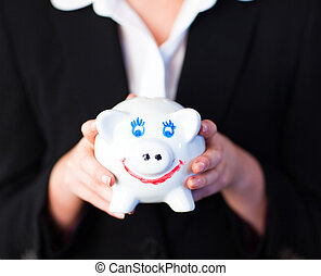 Young woman holding a funky piggy bank