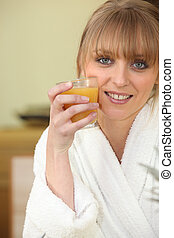 Young woman holding a glass of orange juice