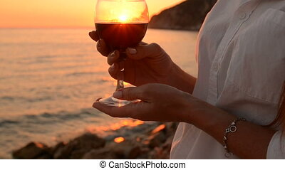 Young woman holding a glass of red wine, sunset by the sea