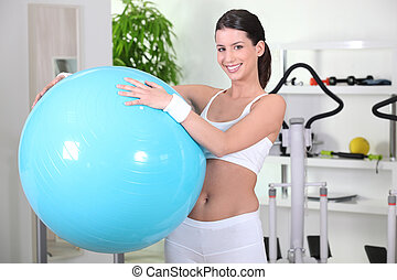 young woman holding a gym ball