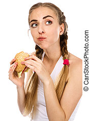 Young woman holding a hamburger and an apple