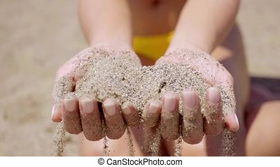 Young woman holding a handful of beach sand