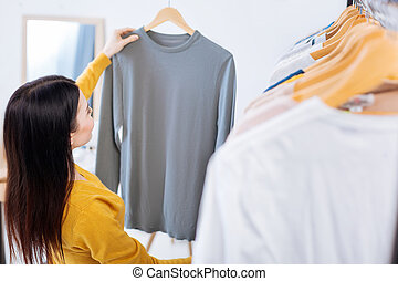 Young woman holding a hanger with a sweater and looking at it