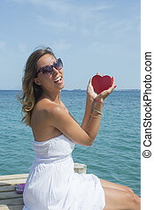 Young woman holding a heart shaped box at the seaside