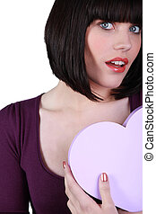 Young woman holding a heart-shaped box