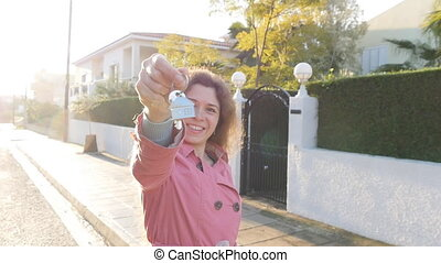 Young woman holding a key in hand from a new house
