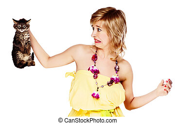 young woman holding a kitten in disgust