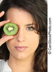 Young woman holding a kiwi