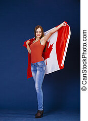Young woman holding a large Canadian flag