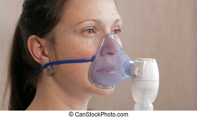 Young woman holding a mask from an inhaler at home. Treats ...