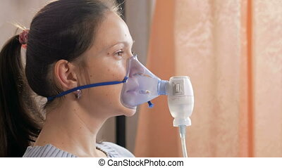 Young woman holding a mask from an inhaler at home. Treats...