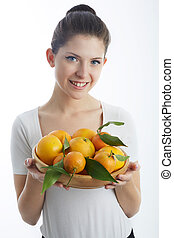 young woman holding a orange fruit