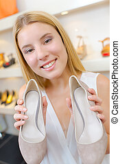 Young woman holding a pair of shoes