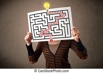 Young woman holding a paper with a labyrinth on it in front...