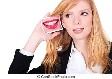 Young woman holding a picture of a mouth to her ear