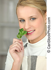Young woman holding a piece of mint to her nose