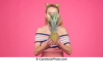 Young woman holding a pineapple on a pink background - Happy...