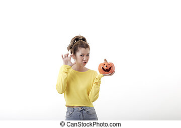 Young woman holding a pumpkin in halloween on white